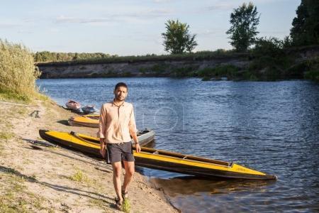 man walking near kayaks on riverside at sunny day