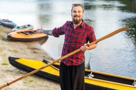 handsome man holding paddle and standing near kayaks on riverside