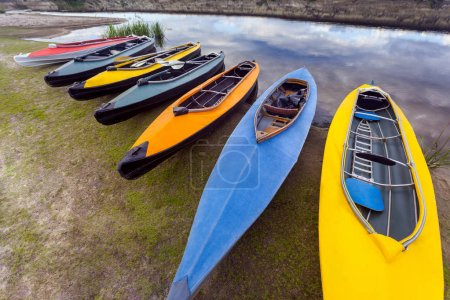 collection of colorful kayaks on riverside at summer day