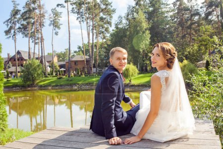 newlyweds turning back and looking at camera while sitting on wooden pier near lake at sunny summer day