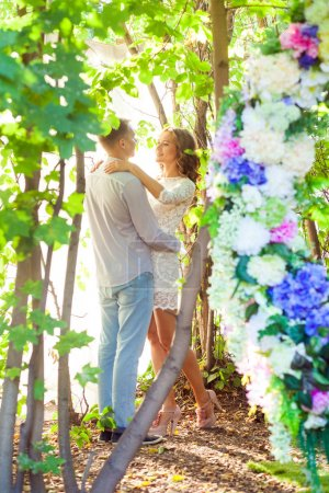 happy couple embracing among trees in spring park, love concept