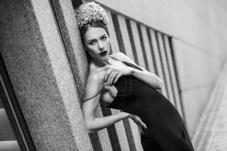 luxurious woman in floral crown and black dress posing while leaning on wall