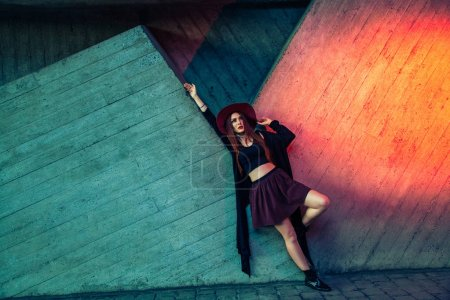 beautiful woman in stylish clothes leaning on colorful wooden building
