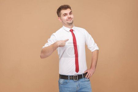 proud businessman pointing finger at himself on light brown background