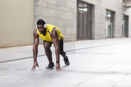 african american athlete man standing in running start pose at street