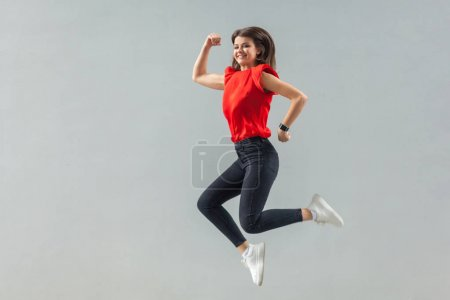 Photo for Full length of happy beautiful brunette young woman in red t-shirt jumping up and looking at camera with toothy smile on gray background - Royalty Free Image