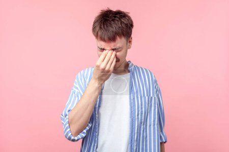 Photo for Portrait of frustrated young brown-haired man in casual striped shirt touching closed eyes, crying from depression, grief or pain, feeling hopeless. indoor studio shot isolated on pink background - Royalty Free Image