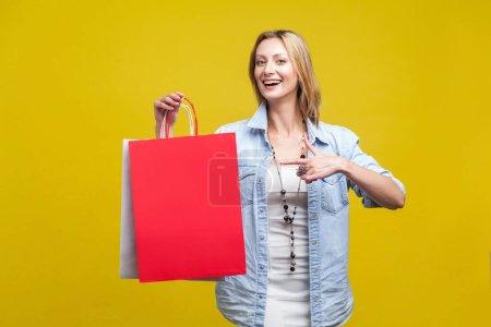 Photo pour Participez au magasinage ! Portrait de la joyeuse cliente du magasin, heureuse femme pointant vers les sacs et regardant la caméra avec le sourire des dents, satisfaite des réductions. studio intérieur isolé sur fond jaune - image libre de droit