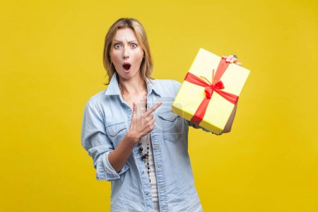Photo pour Wow, what a surprise! Portrait of amazed woman with fair hair in denim casual shirt pointing at wrapped gift box and looking with amazement, shocked by holiday present. studio shot isolated on yellow - image libre de droit