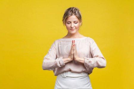 Photo pour Portrait de calme belle jeune femme aux cheveux clairs en blouse beige décontractée debout aux yeux fermés, tenant les mains dans la prière ou le namaste, la méditation. studio intérieur isolé sur fond jaune - image libre de droit
