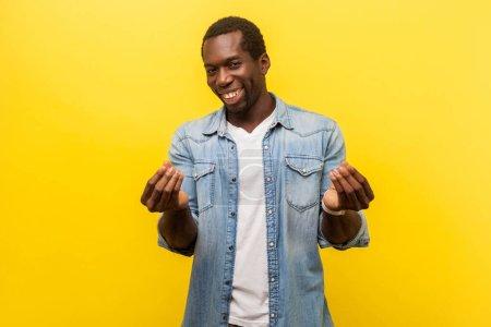Photo pour Portrait de jeune homme intelligent en chemise décontractée en denim regardant la caméra avec le visage rusé et de montrer un geste d'argent avec les doigts, la planification de profit facile. studio intérieur isolé sur fond jaune - image libre de droit