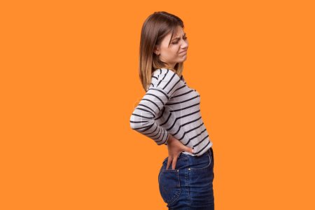 Photo pour Vue de côté portrait de femme malade aux cheveux bruns en chemise à rayures à manches longues debout avec grimace de douleur, se retenant, souffrant de maux de dos forts. studio intérieur tourné isolé sur fond orange - image libre de droit