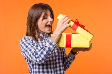 Photo pour Portrait de charmante jeune femme aux cheveux bruns portant une chemise à carreaux décontractée regardant dans la boîte cadeau non emballée, curieuse de la surprise d'anniversaire. studio intérieur isolé sur fond orange - image libre de droit
