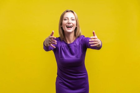 Photo pour Come into my arms, free hugs! Portrait of adorable hospitable woman in elegant tight purple dress smiling and reaching out hands, going to embrace. indoor studio shot isolated on yellow background - image libre de droit