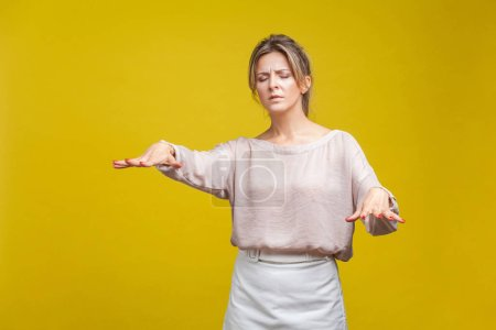 Photo pour Portrait of disoriented blind young woman with fair hair in casual beige blouse standing with stretched arms, searching for way. vision problems. indoor studio shot isolated on yellow background - image libre de droit