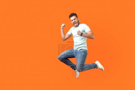 Photo pour Side view of extremely happy man in white outfit jumping in air with raised arm gesturing yes i did it, I'm winner, screaming loud for joy feeling energetic and lively. isolated on orange background - image libre de droit
