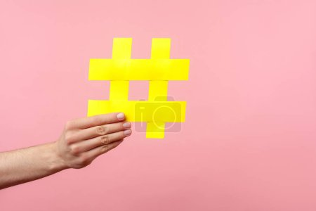 Photo pour Closeup of male hand holding large yellow hashtag sign, concept of marketing and promotion in internet, followers in social media, trend content. indoor studio shot isolated on pink background - image libre de droit