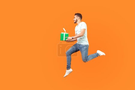 Photo pour Full length portrait of excited happy brunette man in sneakers and denim outfit flying or running in air with gift box, holiday present, hurrying for sale. studio shot isolated on orange background - image libre de droit