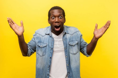 Photo for Wow, it's unbelievable! Portrait of bewildered shocked man in denim casual shirt staring at camera with widely open mouth and big eyes, raising arms in amazement. indoor studio shot isolated on yellow - Royalty Free Image