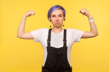 Photo pour I'm strong and independent! Portrait of self-confident hipster girl with violet short hair in denim overalls raising hands to show biceps, feeling power. isolated on yellow background, studio shot - image libre de droit