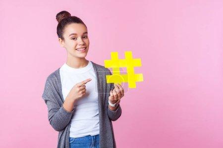 Photo pour Regardez le contenu populaire ! Portrait d'une adolescente brune à la mode avec une coiffure blonde en tenue décontractée souriante et pointant vers le grand symbole jaune du hashtag. studio intérieur isolé sur fond rose - image libre de droit
