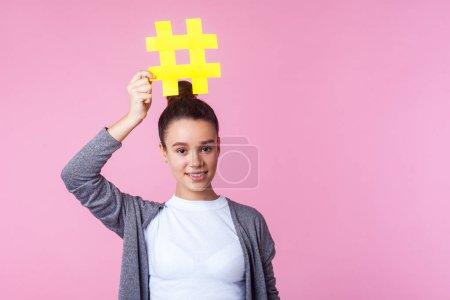 Photo pour Blogger publicité. Portrait d'une adolescente brune branchée à la coiffure blonde en tenue décontractée, souriante et tenant au-dessus de la tête un gros symbole de tag haché. studio intérieur isolé sur fond rose - image libre de droit