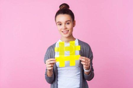 Photo pour Contenu populaire, promotion ! Portrait d'une adolescente brune branchée à la coiffure chic, vêtue de vêtements décontractés, souriant et tenant un grand symbole de hashtag jaune. studio intérieur isolé sur fond rose - image libre de droit