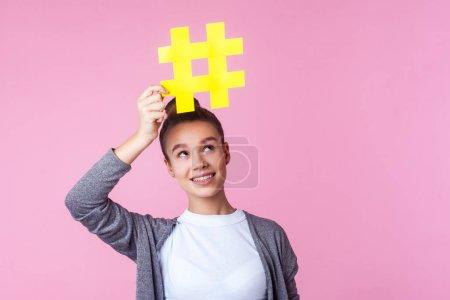 Photo pour Promotion des blogs. Portrait d'une adolescente brune branchée à la coiffure blonde en tenue décontractée, souriante et regardant le grand symbole du hashtag au-dessus de sa tête. studio intérieur isolé sur fond rose - image libre de droit