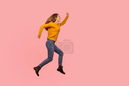 Photo pour Portrait complet d'une jeune fille de gingembre excitée en chandail et en denim sautant à l'air ou en volant, courant à toute vitesse quelque part, énergique et enthousiaste criant de bonheur. photo de studio, fond rose - image libre de droit