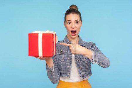 Photo pour Wow, c'est un cadeau magnifique ! Portrait d'une femme étonnée et étonnée, vêtue à la mode, avec une blouse pointant vers la boîte à cadeaux rouge et regardant l'appareil photo au visage choqué. prise de vue isolée sur fond bleu - image libre de droit