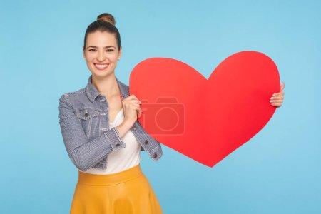 Photo pour Belle femme heureuse vêtue à la mode avec un sourire aimable tenant grand coeur de papier rouge, exprimant l'affection d'amour, symbole de charité et de gentillesse. studio intérieur tourné isolé sur fond bleu - image libre de droit
