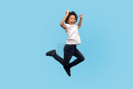 Photo for Full length, lively energetic little boy in T-shirt and denim jumping in air screaming with happiness, child flying up, feeling inspired crazy and overjoyed. indoor studio shot, blue background - Royalty Free Image