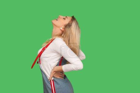 Photo pour Problèmes de colonne. Portrait d'une femme adulte malsaine en salopette en denim criant dans un mal de dos aigu, souffrant d'inflammation rénale, nerf pincé. studio intérieur tourné isolé sur fond vert - image libre de droit