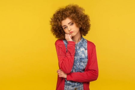 Photo for Bored tired lazy woman with curly hair leaning on hand and looking at camera with apathetic indifferent expression, listening boring conversation. indoor studio shot isolated on yellow background - Royalty Free Image