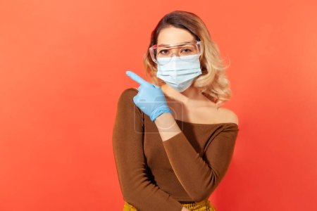 Photo for Look tips against coronavirus pandemic! Woman wearing hygienic face mask, gloves and protective glasses pointing blank advertising area, copy space for 2019-ncov info. indoor studio shot isolated - Royalty Free Image