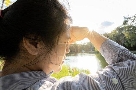 Photo pour Femme asiatique ont conjonctivite, cataracte, jeune femme couvrant le visage à la main de soleil brillant en plein air le jour ensoleillé, sensation de vertige, risque de dommages oculaires par ultraviole (rayons UV), photophobie, concept de santé oculaire - image libre de droit