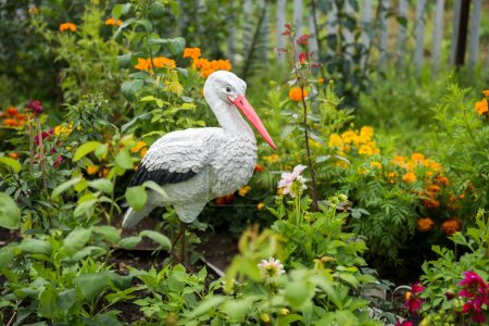 Decoration for the flower garden, the bird stork stands among the flowers.