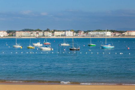 Ciboure, France - Sept 26, 2016: Ciboure beach with few tourist and Saint jean de Luz bay with luxurious boats on background