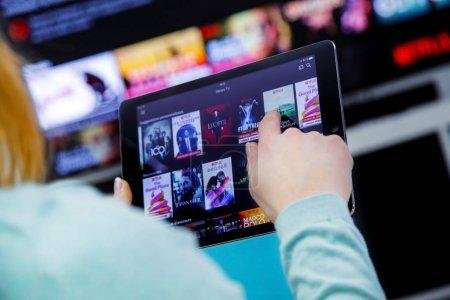 Photo pour Benon, France - 21 janvier 2018: Femme tenant une tablette tactile et commutation des canaux sur la page d'accueil de France Netflix. avec le téléviseur sur le fond. Netflix Inc. est une société multinationale américaine du divertissement fondée sur 1997 - image libre de droit