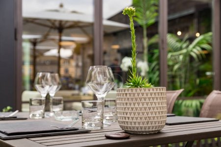 cutlery of a gourmet restaurant table with greenery in the background