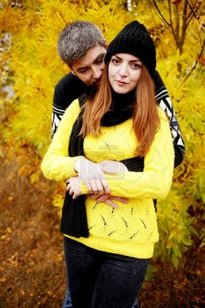 Photo for Man tenderly hugging woman from behind in beautiful autumn park - Royalty Free Image