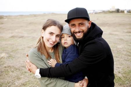 joyful family embracing on meadow
