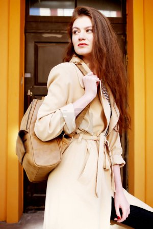 young woman in beige trench coat