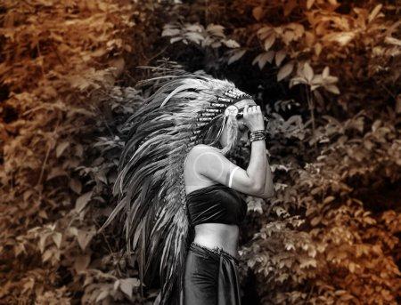 Photo pour La belle femme soulevant coiffe toucher la main faite de plumes d'oiseaux. couleur bleue peinte sur sa joue, portrait de mannequin posant, jungle dans la forêt, ton noir et blanc, lumière floue autour - image libre de droit