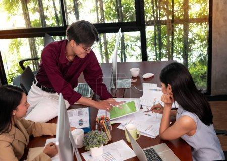 Photo pour Jeunes gens d'affaires travaillant, avec des collègues réunion d'équipe, temps chargé, au bureau, lumière floue autour - image libre de droit
