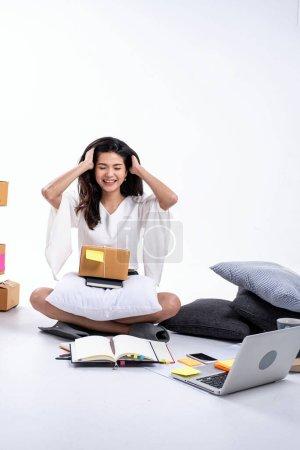 Photo pour La belle dame assise sur le sol, lever la main toucher sa tête avec un sentiment heureux, vérifier la commande et l'emballage boîte aux lettres, la vente en ligne à la maison - image libre de droit