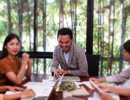 Foto de En el enfoque selectivo de un hombre guapo. Reunión de directores con un equipo de jóvenes colegas desenfocado, en el cargo, oscurece la luz alrededor. - Imagen libre de derechos