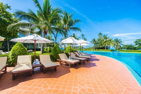Photo pour Superbe parasol de luxe et chaise autour de la piscine extérieure à l'hôtel et station balnéaire avec cocotier sur ciel bleu - Boostez la couleur Traitement - image libre de droit