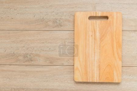 Photo for Wood cutting board on wooden background with copy space - Royalty Free Image