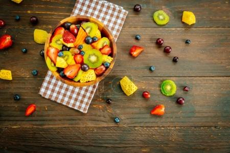 Mixed and assorted fruits with kiwi strawberry grape and other in bowl on wood table - Filter Processing